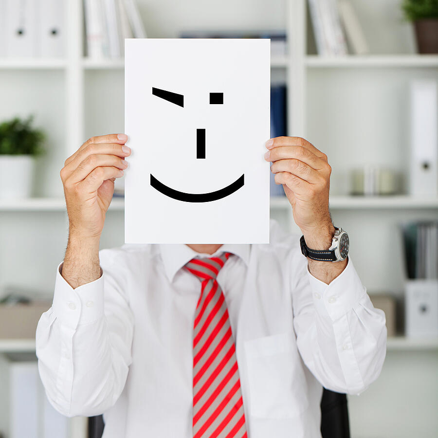 Mature businessman holding wink smiley in front of his face at office